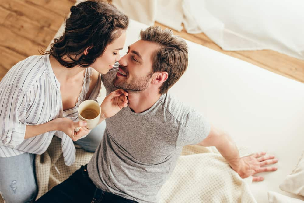 couple flirting with eachother on bed holding coffee in mugs - relationship bucket list goals