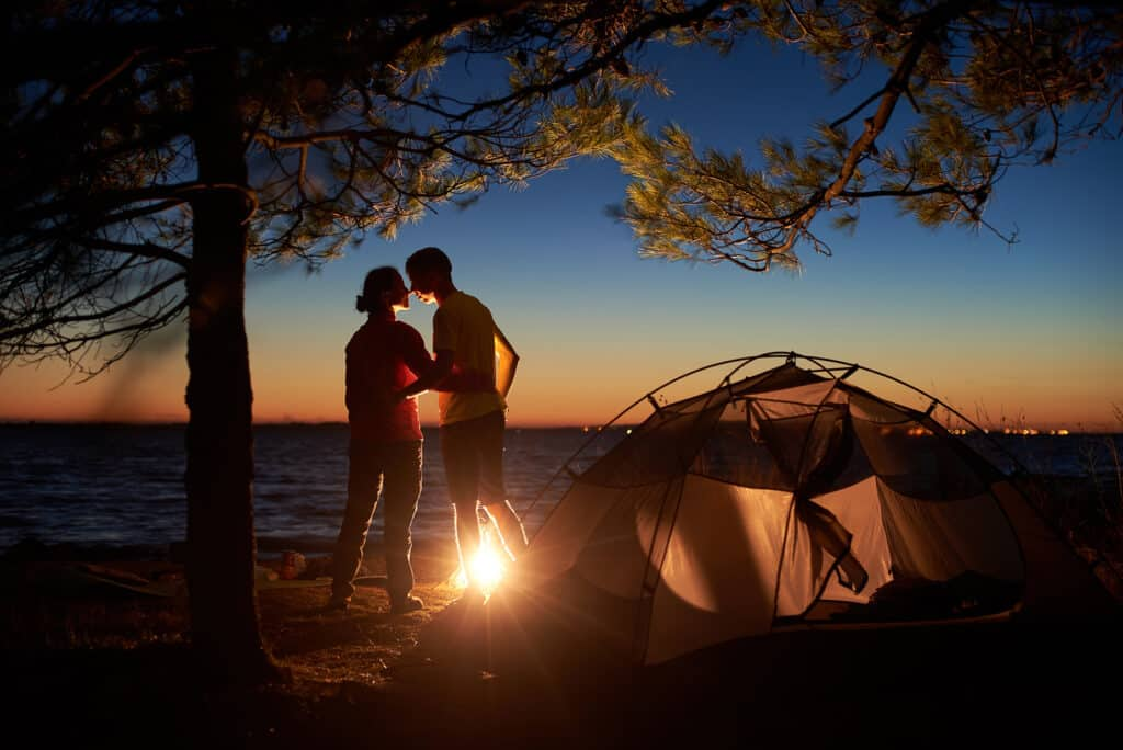 couples adventure bucket list - Night camping under tree at sea. Silhouettes of hiker couple, back view of man and woman stand at campfire, embracing near tourist tent in evening. Tourism, happy relations and outdoor camping concept