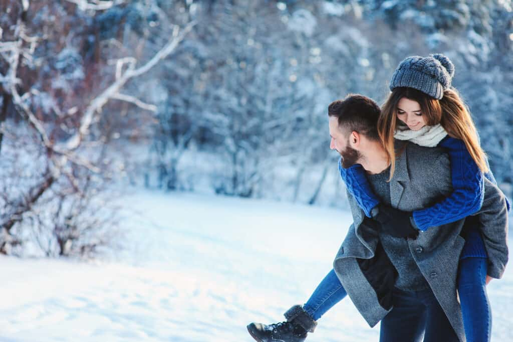 couple walking in snow man giving woman a piggy back