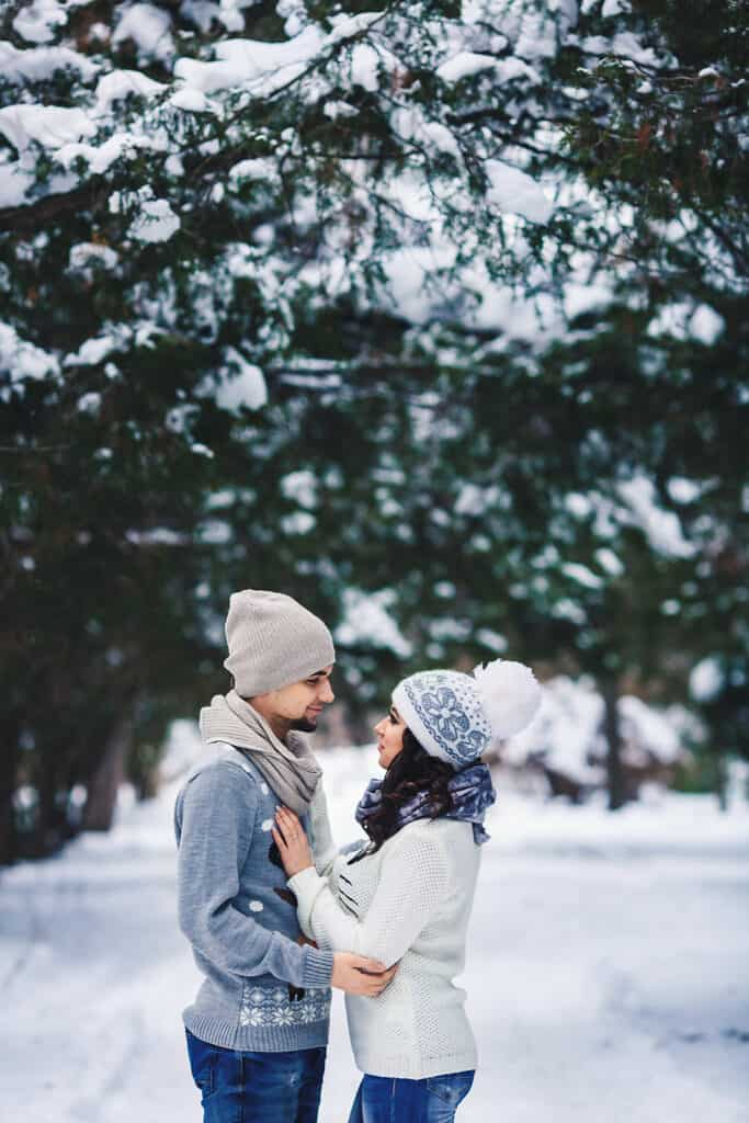 couple laughing and smiling together in snowy woods